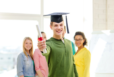education and people concept - smiling male student with diploma and corner-cap and friends on the back Stock Photo