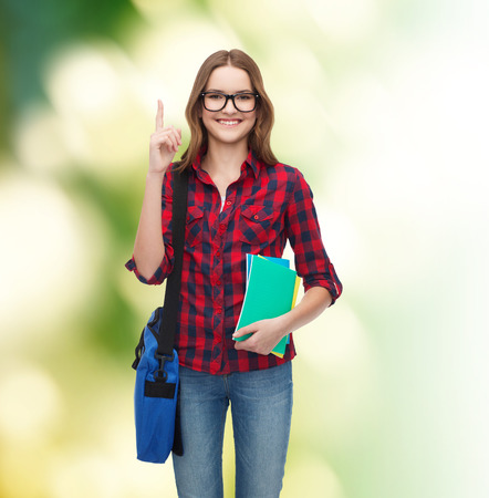 education and people concept - smiling female student in eyeglasses with bag and notebooks showing finger up over green background photo