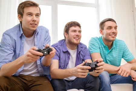 jugando videojuegos: la amistad, la tecnología, los juegos y el concepto de casa - sonriendo amigos masculinos que juegan juegos de video en casa
