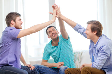 hands high: teamwork, friendship and happiness concept - smiling male friends giving high five at home Stock Photo