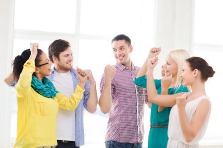 business, office, startup, success and victory concept - happy creative team celebrating victory in office photo