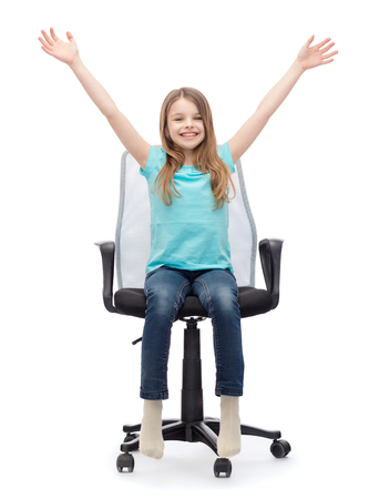 education, celebration, office and happy people concept - smiling little girl sitting in big office chair with hands up photo