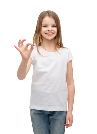 ok sign: happy people and gesture concept - smiling little girl in blank white t-shirt showing ok gesture