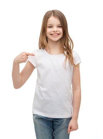 t シャツ デザイン コンセプト - 自分自身を指している空白白い t シャツの少女の笑顔 写真素材