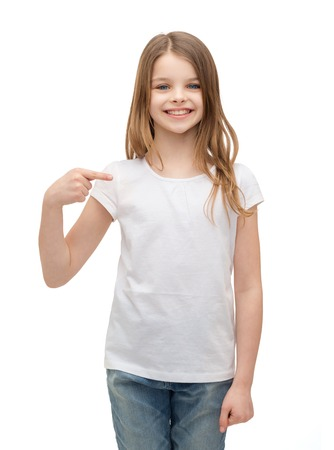 t-shirt design concept - smiling little girl in blank white t-shirt pointing at herself Stock Photo - 28781500