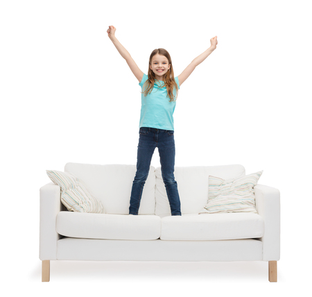 home, leisure and happiness concept - smiling little girl jumping or dancing on sofa photo