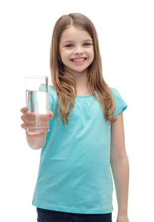 health and beauty concept - smiling little girl giving glass of water photo