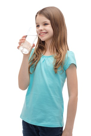 health and beauty concept - smiling little girl with glass of water photo