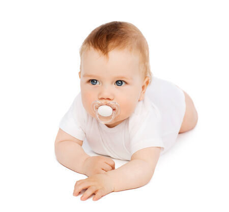 suck: child and toddler concept - smiling baby lying on floor with dummy in mouth