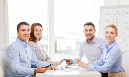 business, technology and office concept - smiling business team with smartphones having meeting in office photo