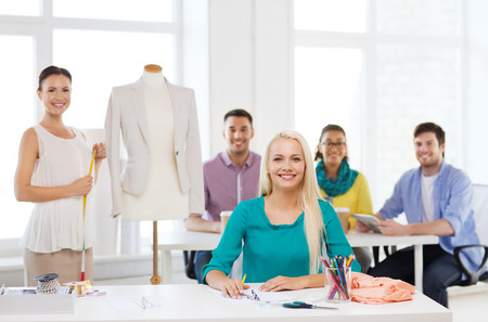 startup, education, fashion and office concept - smiling designers drawing sketches and measuring jacket on mannequin in office photo