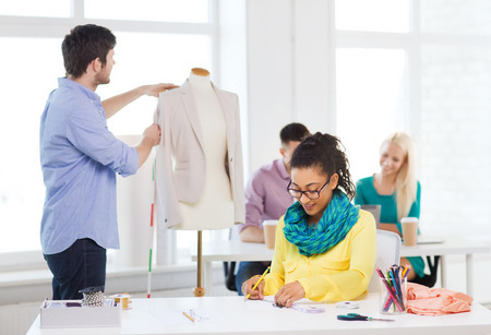 startup, education, fashion and office concept - smiling female drawing sketches and male measuring jacket on mannequin in office photo