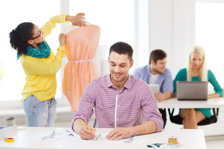 startup, education, fashion and office concept - smiling male drawing sketches and female adjusting dress on mannequin in office photo