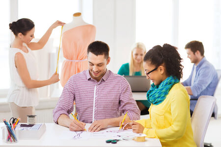 styling: startup, education, fashion and office concept - smiling designers drawing sketches and adjusting dress on mannequin in office