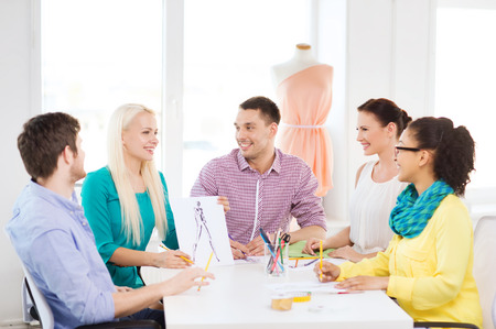 startup, education, fashion and office concept - smiling fashion designers working in office photo