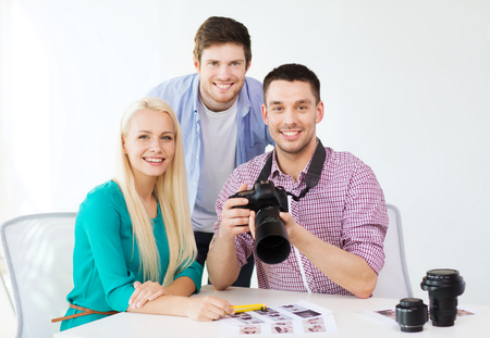 business, education, office and startup concept - smiling creative team with photocamera working in office photo