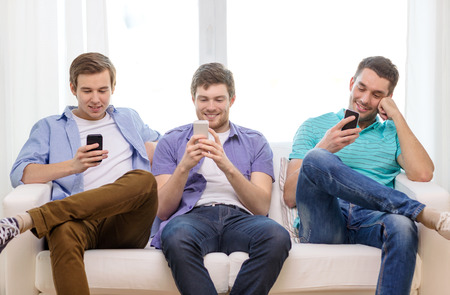 friendship, technology and home concept - smiling male friends with smartphones at home photo