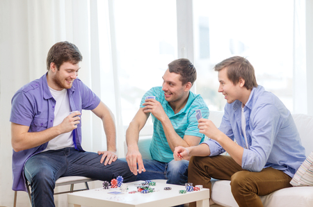 card game: leisure, games and lifestyle concept - happy three male friends playing poker at home Stock Photo