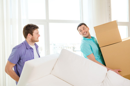 packing: moving, real estate and friendship concept - smiling male friends with sofa and boxes at new home
