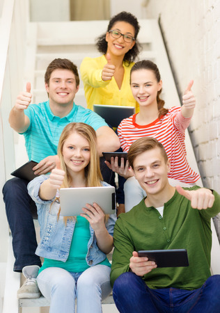 education and technology concept - smiling students with tablet pc computer sitting on staircase and showing thumbs up photo