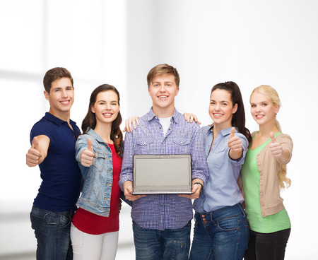 education, advertisement and new technology concept - smiling students with laptop computer blank screen showing thumbs up photo