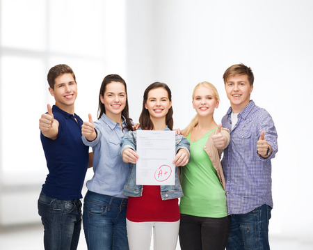 education and people concept - group of smiling students standing and showing test and thumbs up photo