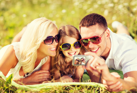 summer holidays, children and people concept - happy family with camera, blue sky and green grass taking picture photo