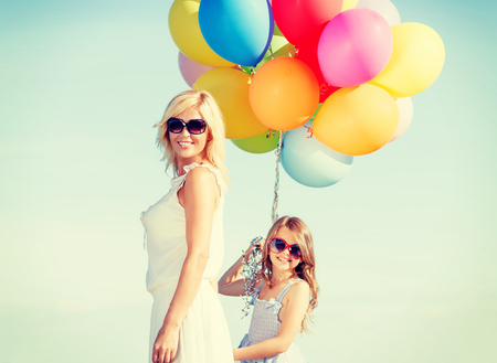 summer holidays, celebration, family, children and people concept - mother and child with colorful balloons photo