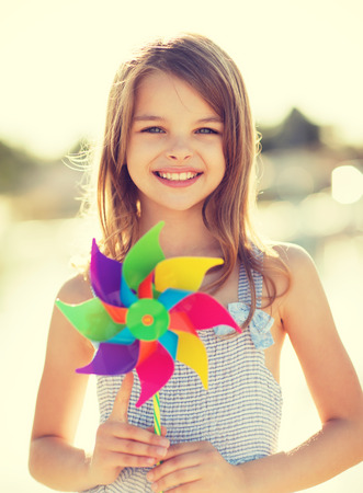 summer holidays, celebration, family, children and people concept - happy girl with colorful pinwheel toy photo