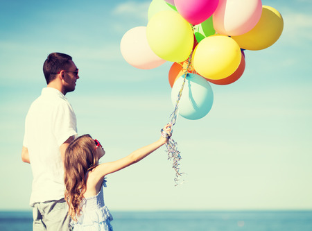 summer holidays, celebration, children and family concept - father and daughter with colorful balloons photo