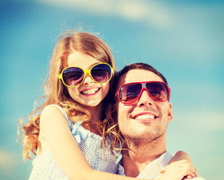 summer holidays, children and people concept - happy father and child in sunglasses over blue sky photo
