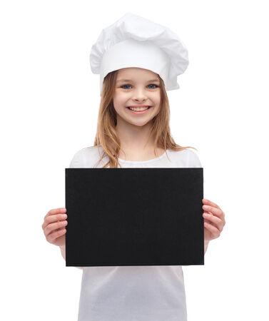 cooking, advertisement and food concept - smiling little chef, cook or baker with blank black paper photo