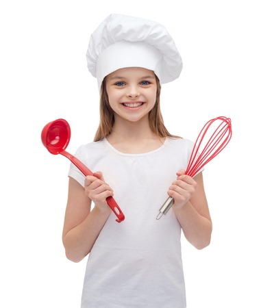 cooking utensils: cooking and people concept - smiling little girl in cook hat with ladle and whisk