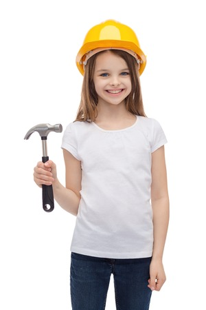 construction and people concept - smiling little girl in protective helmet with hammer photo