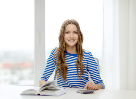education and home concept - happy smiling student girl with notebook, calculator and book photo