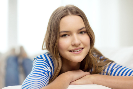 home and happiness concept - smiling teenage girl lying on sofa at home photo