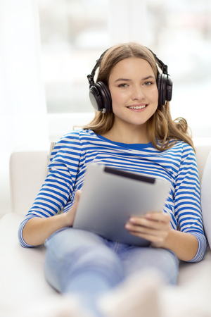 home, music, technology and internet concept - smiling teenage girl lying on the couch with tablet pc computer and headphones at home photo