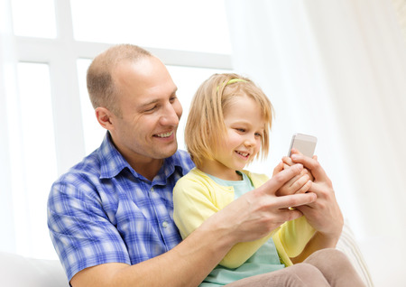 family, children, parenthood, technology and internet concept - happy father and daughter with smartphone at home photo