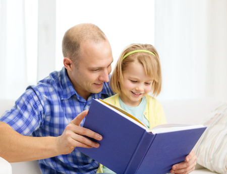 family, children, education, school and happy people concept - smiling father and daughter with book at home photo