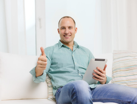 technology and lifestyle, distance learning concept - handsome man working with tablet pc at home and showing thumbs up photo
