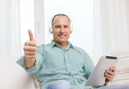 technology and lifestyle, distance learning concept - handsome man with tablet pc computer and headphones at home showing thumbs up photo
