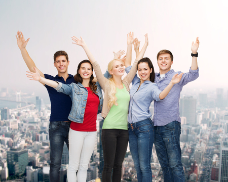 welcoming: education and people concept - group of smiling students standing and waving hands