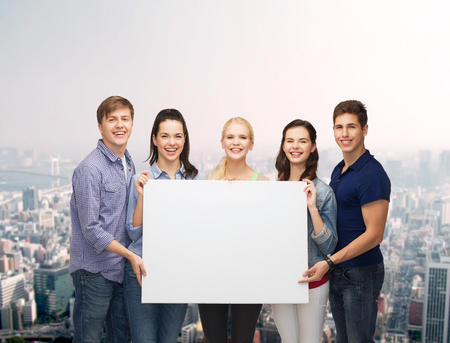 sales team: education and people concept - group of standing smiling students with white blank board