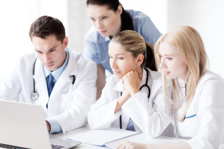 medical cabinet: healthcare, medical and technology concept - group of doctors looking at laptop