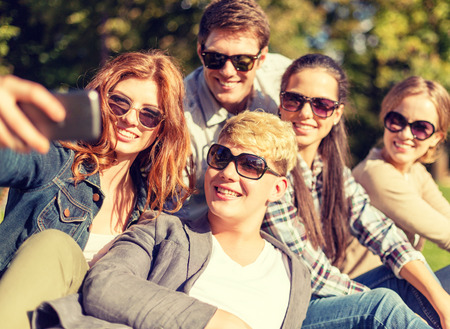 happy teenagers: summer, internet, social networking, technology and teenage concept - group of teenagers taking photo with smartphone camera outside
