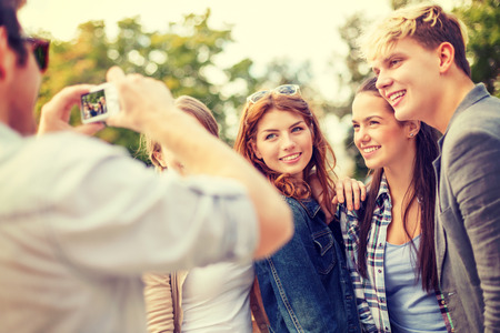 summer holidays, electronics and teenage concept - group of smiling teenagers taking photo with digital camera outside photo