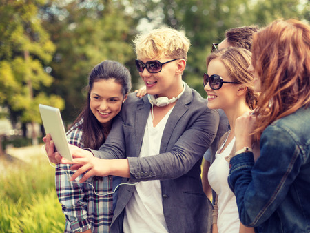 summer, internet, social networking, technology and teenage concept - group of teenagers taking photo with tablet pc outside photo