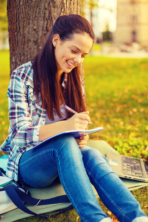 education, campus and people concept - smiling teenager writing in notebook photo