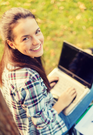 education technology: education, technology and internet concept - smiling teenager with laptop computer