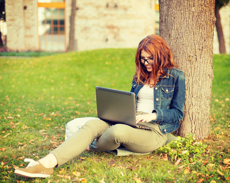 education, technology and internet concept - smiling redhead teenager in eyeglasses with laptop computer photo